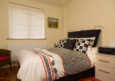 Bedroom with black & white cushions and white venetian blind