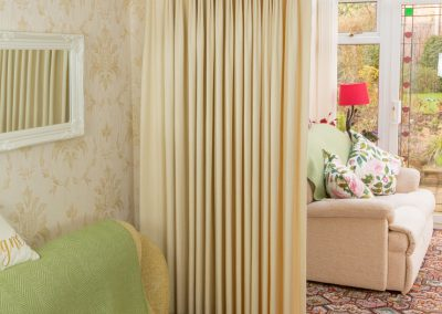 Full length cream curtains on a gold pole