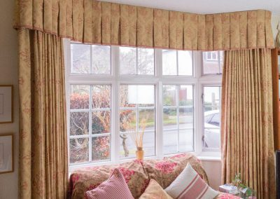 Full length curtains with matching pelmet in a bay window