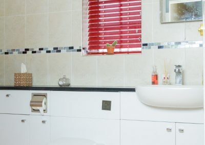 Red metal venetian blind in bathroom