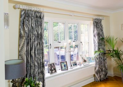 Large window with full length triple pleated curtains pulled back