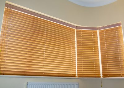 Three wooden venetian blinds covering a curved window