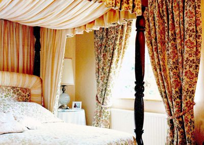 Full length pleated curtains, with rope-style tie backs and matching pelmet on a four-poster bed