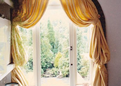 Full length curtains in an arch and tied-back