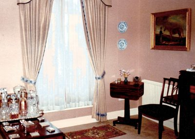 Full length, tied-back curtains with matching pelmet