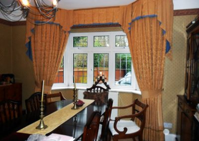 Elaborate floor-length curtains and pelmet at a bay window