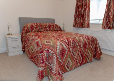 Red & green diamond patterned bed throw with matching curtains