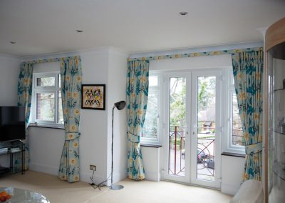 Two pairs of full length curtains with matching tie-backs and small pelmet