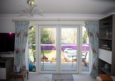 Floor length pleated curtains with ornate hold-backs